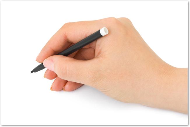 黒いペンで何かを書こうとしている男性の手