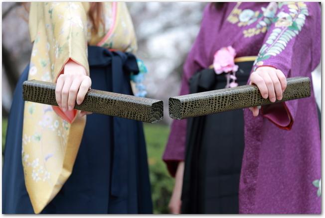 卒業証書の筒を持った袴姿の女性の様子