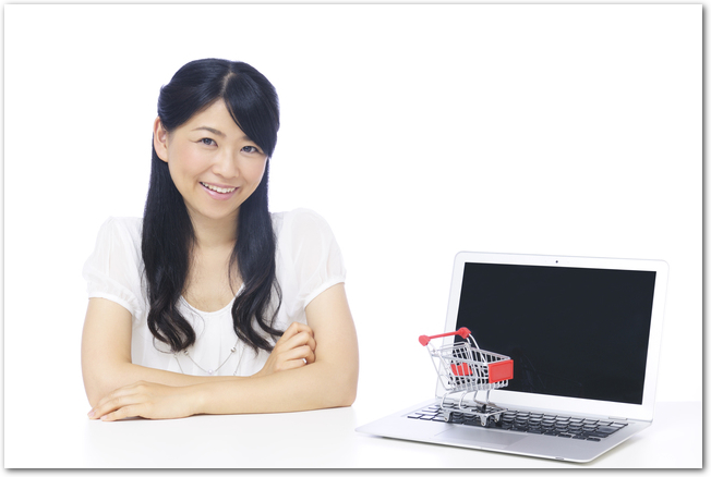 女性とパソコンに乗った小さいショッピングカートの模型