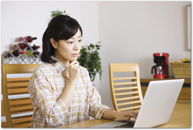 リビングでパソコンの画面を見る母親の様子