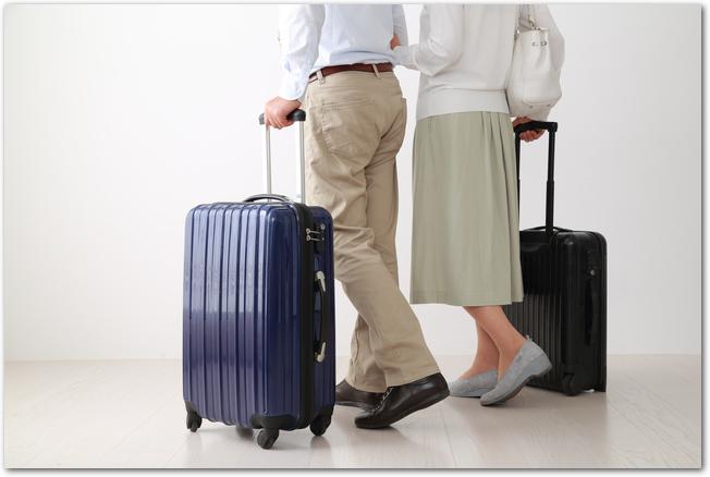 ハードタイプとソフトタイプのスーツケースを持つ夫婦