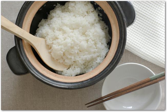 黒い土鍋とお茶碗に盛られたご飯