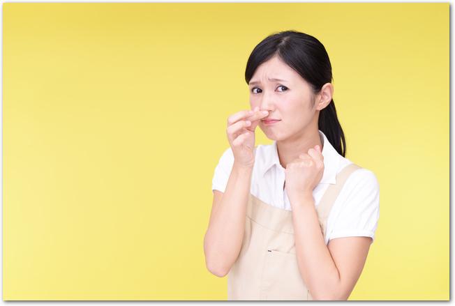 悪臭に鼻を押さえる女性の様子