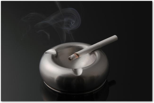 灰皿に置かれたタバコから立ち上る煙