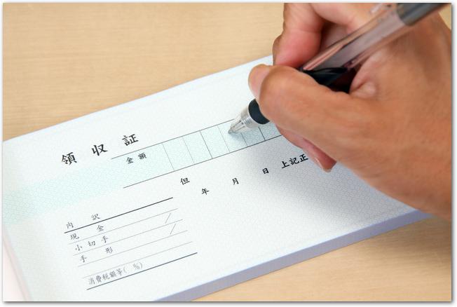 ボールペンで領収書に記入している手元