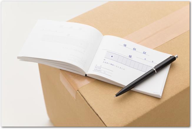 ダンボールの上に置かれた領収書とボールペン