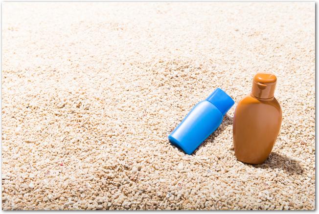 砂の上に置かれた日焼け止めの容器