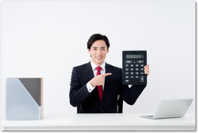 電卓を指さすビジネスマン