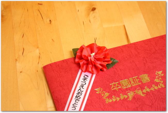 フローリングに置かれた赤い卒園証書
