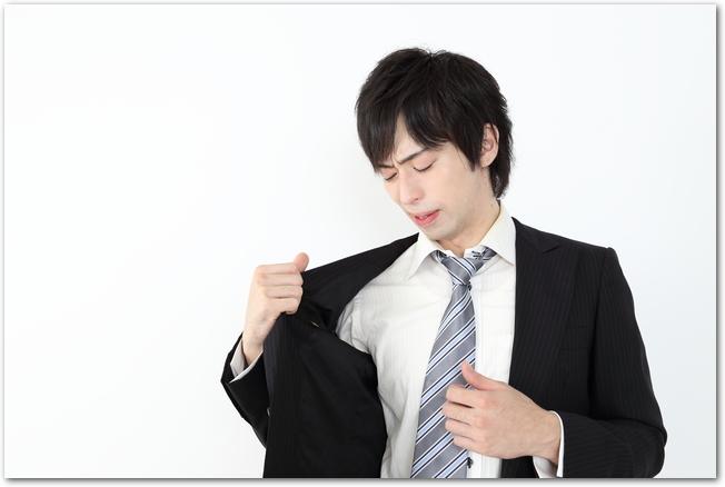 脇の部分を見るスーツ姿のサラリーマン