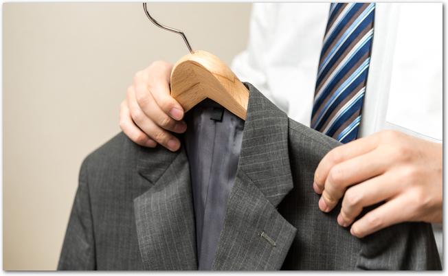 スーツをハンガーにかける男性の手元