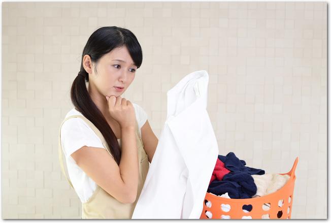 洗濯物を手に悩んだ表情を浮かべる主婦