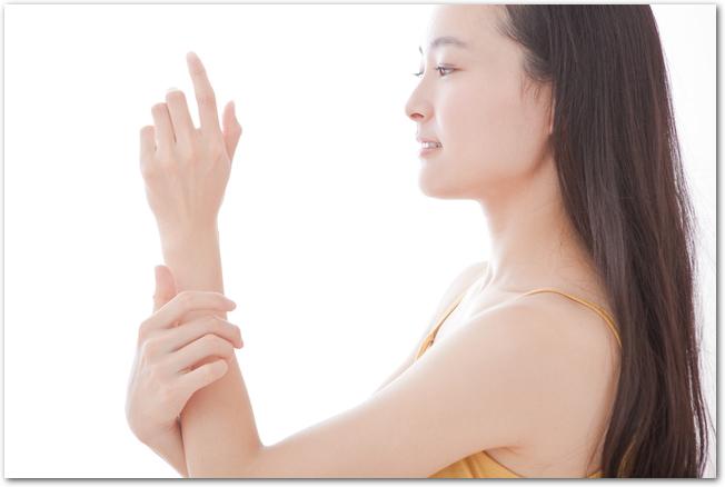 腕に日焼け止めを塗る女性の様子