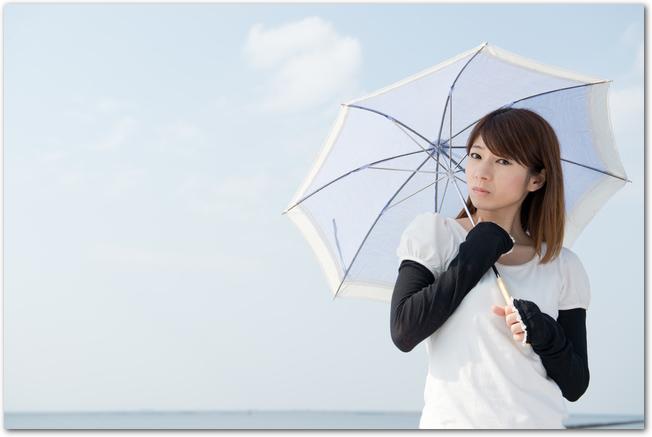 日傘をさしてアームカバーをした女性