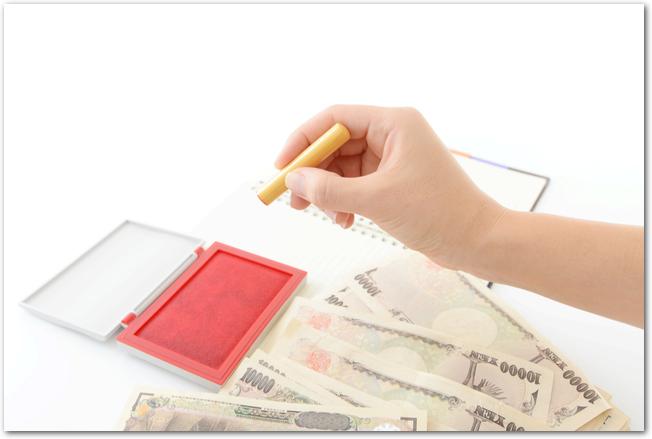 扇型に並べられた一万円札と朱肉と印鑑