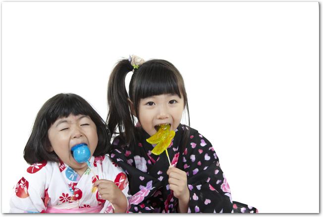 リンゴ飴を食べる浴衣姿の姉妹