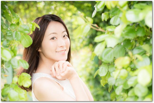 新緑の中で微笑む女性の様子