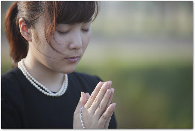 数珠を手に拝む女性の様子