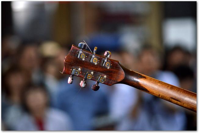 演奏中のギターヘッドごしに見える大勢の聴衆たち