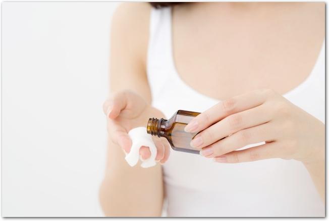 化粧水をコットンに染み込ませている女性の手元