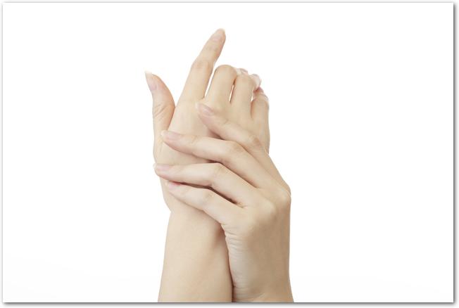 左手で右手の甲を押さえている女性の手