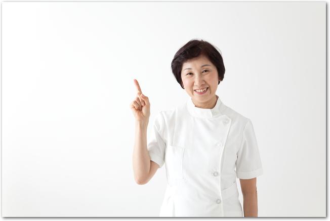 人差し指を立てる看護師のミドル女性
