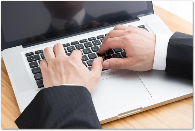 ノートパソコンのキーボードを打つビジネスマンの手元