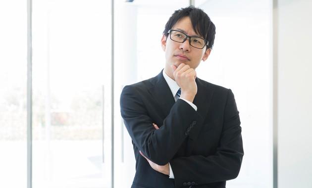 アゴに手を当てて考えるスーツ姿のビジネスマン