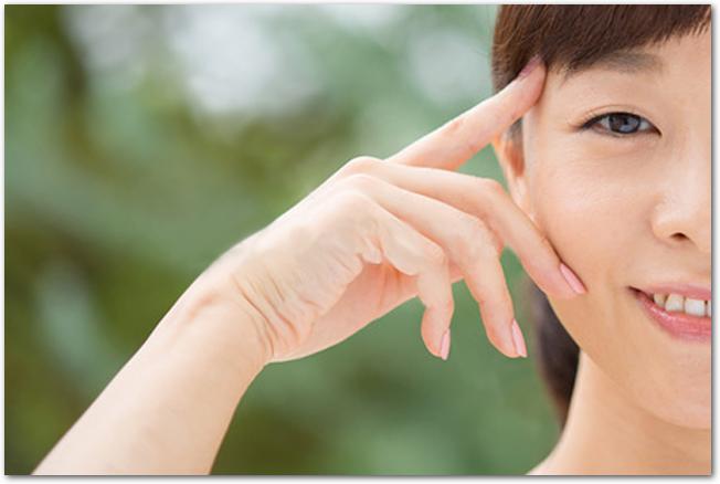 目元に指を当てる笑顔の女性の様子