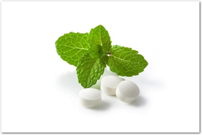 白い背景に置かれたミントの葉と白い錠剤
