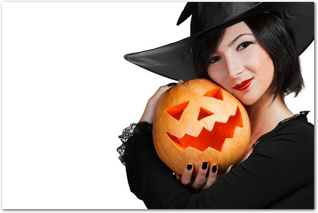 ジャックオランタンを抱きかかえている魔女のコスプレをした女性
