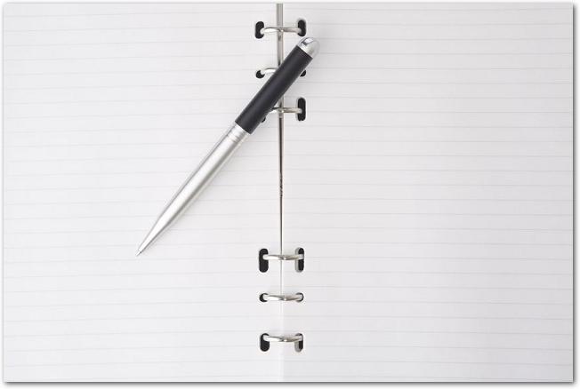 開いたノートの上にボールペンが置かれている様子