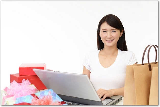 ノートパソコンでネットショッピングをしている女性の様子