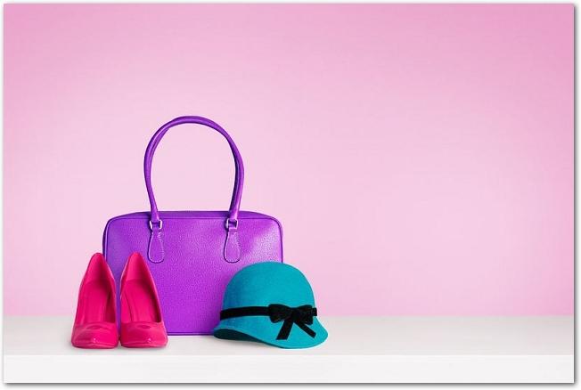 ピンクの背景に置かれた帽子やバッグなどのファッション小物