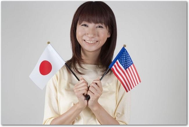日本とアメリカの国旗を持つ笑顔の女性の様子