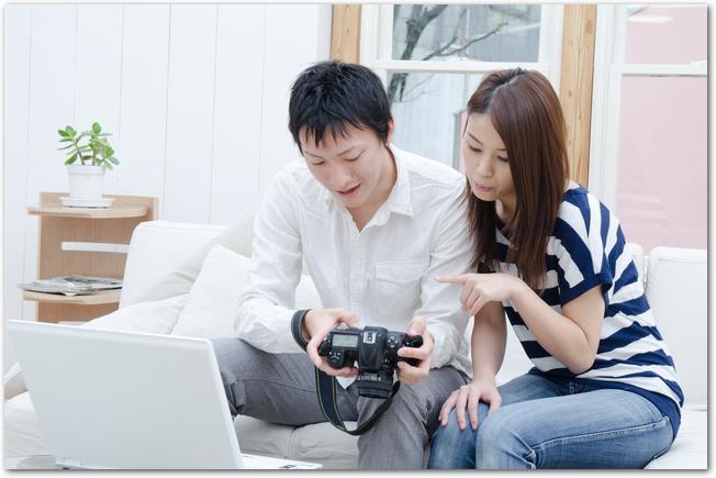 写真入りの引っ越しハガキを作成している若い夫婦