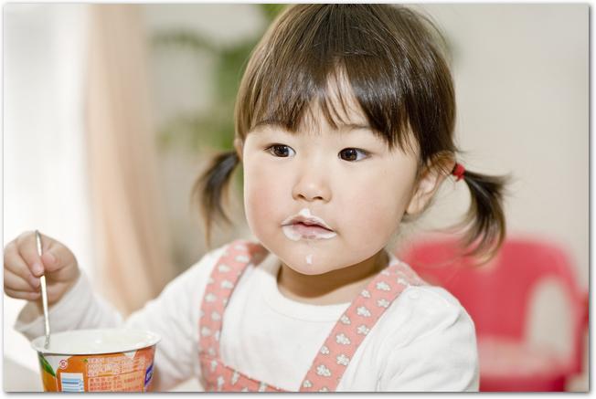 ヨーグルトを食べる小さな女の子