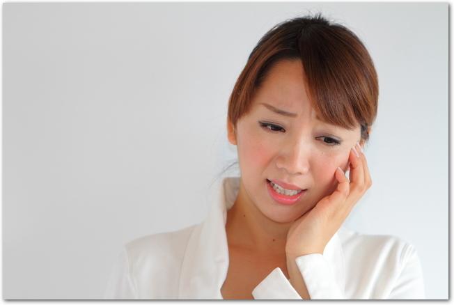 頬の腫れに悩まされる若い女性