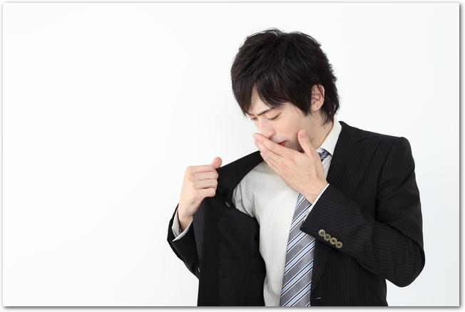 自分のスーツの臭いが気になっている若い男性