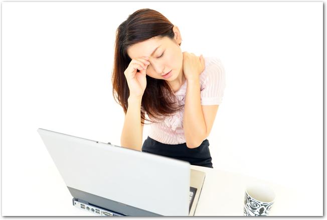 肩こりと頭痛に苦しむ若い女性