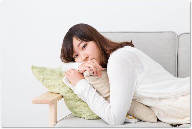 生理痛でダルそうにソファに横たわる女性