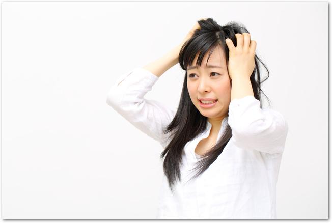 頭をかいている若い女性